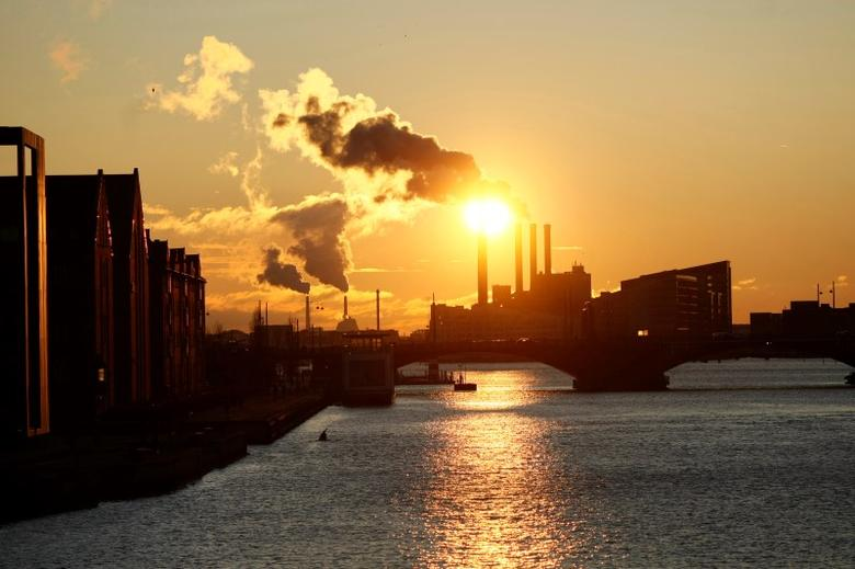 The Sun sets over a smoking power plant in Copenhagen December 12, 2009. REUTERS/Christian Charisius