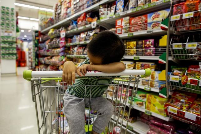 A boy sleeps in a shopping cart at a department store in Bangkok October 29, 2013. REUTERS/Athit Perawongmetha
