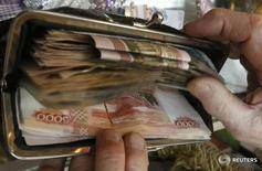 Продавец складывает полученные за день деньги в кошелек. Федеральный бюджет РФ в январе-мае был исполнен с дефицитом 1,49 триллиона рублей, или 4,6 процента ВВП, а в январе-апреле он был исполнен с дефицитом 1,23 триллиона рублей, или 4,7 процента ВВП, сообщил Минфин РФ во вторник. REUTERS/Ilya Naymushin