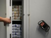 Las principales aseguradoras de Europa están vendiendo protección a los bancos alemanes que guardan miles de millones de euros en cámaras acorazadas para evitar pagar la penalización por depositar dinero en el Banco Central Europeo, dijeron a Reuters ejecutivos de compañías. En la imagen de archivo, un empleado de un banco austríaco abre una caja fuerte con billetes de 50 y 20 euros en Viena, el 22 de julio de 2013. REUTERS/Leonhard Foeger