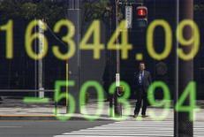 Una persona se refleja en una pantalla que muestra el índice Nikkei de Japón, afuera de una correduría en Tokio, Japón. 18 de abril de 2016. Las acciones japonesas subieron en una sesión volátil el miércoles, cortando una racha de cuatro días de caídas gracias a la cobertura de posiciones cortas antes de las reuniones de algunos bancos centrales importantes. REUTERS/Toru Hanai