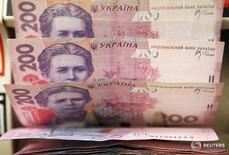 Кассир пеерсчитывает украинские гривны в магазине в Киеве. Украина легче справится с проблемами бюджета и платежного баланса, если Международный валютный фонд выделит хотя бы $1 миллиард в этом году, пока страна возвращается на путь реформ, сказал советник правительства.  REUTERS/Konstantin Chernichkin