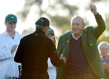 Apr 7, 2016; Augusta, GA, USA; Arnold Palmer (right) waves to the gallery as he shakes hands with Gary Player on the first tee during the first round of the 2016 The Masters golf tournament at Augusta National Golf Club. Mandatory Credit: Michael Madrid-USA TODAY Sports