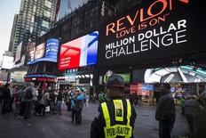 """A Public Safety officer keeps watch as people stand in front of  a billboard owned by Revlon that takes their pictures and displays them in Times Square in the Manhattan borough of New York October 13, 2015. Cosmetics company Revlon switched on its """"Kiss Cam"""" in New York's Times Square on Tuesday, four days after the interactive billboard went dark over complaints that it was attracting gropers. REUTERS/Carlo Allegri - RTS4CDM"""