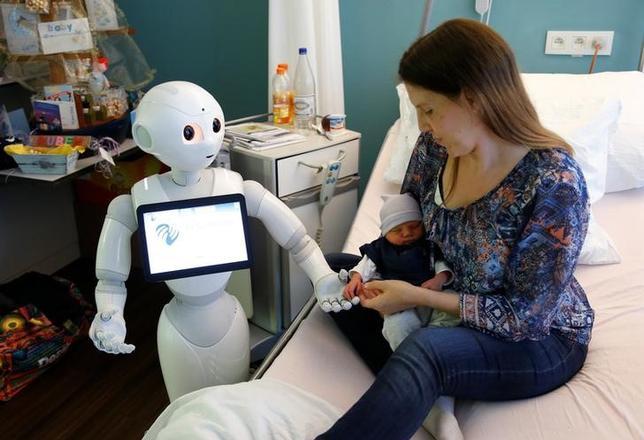 6月17日、ソフトバンクが開発したヒト型ロボット「Pepper(ペッパー)」が、ベルギーの病院で受付係として採用された。写真は新生児の手を握るペッパー。16日撮影(2016年 ロイター/Francois Lenoir)