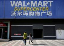 Pedestrians walk past a signboard of Wal-Mart at its branch store in Beijing, China, October 15, 2015.   REUTERS/Kim Kyung-Hoon/File Photo
