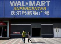 Peatones caminan cerca de la entrada de una sucursal de Wal-Mart en Pekín, China. 15 de octubre de 2015. Wal-Mart Stores Inc vendió su tienda de abarrotes online en China a cambio de una participación en la segunda empresa más grande de comercio electrónico en el país, destrozando su estrategia previa para impulsar ventas menguantes en uno de los mercados minoristas más difíciles del mundo. REUTERS/Kim Kyung-Hoon/File Photo