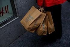 El minorista sueco de moda Hennes & Mauritz anunció el miércoles una caída del 17 por ciento del beneficio en el segundo trimestre por una débil demanda de su ropa de primavera combinado con altos costes. En la imagen, una clienta con bolsas de compra ante una tienda de de H&M en un distrito comercial del centro de Madrid, el 11 de mayo de 2016. REUTERS/Susana Vera