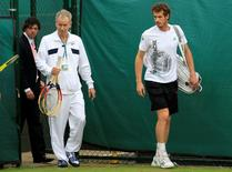 Andy Murray of Britain (R) walks on to a practise court with former Wimbledon champion John McEnroe (C) and U.S. Open golf champion, Rory McIlroy  at the Wimbledon tennis championships in London June 28, 2011.        REUTERS/Suzanne Plunkett