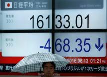 Un peatón camina junto a un tablero electrónico que muestra el índice Nikkei, afuera de una correduría en Tokio, Japón. 13 de junio de 2016. El índice Nikkei de la bolsa de Tokio cayó el miércoles, luego de que los inversores recogieron ganancias antes de un referendo en el Reino Unido que podría perturbar a los mercado más tarde este semana. REUTERS/Issei Kato