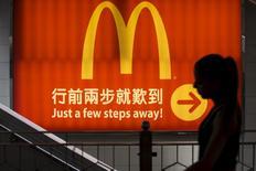 Foto de archivo de una mujer caminando cerca de un local de McDonald's en Hong Kong, China. 25 de julio de 2014. McDonald's Corp ha recibido más de media docena de ofertas por sus locales en China y Hong Kong, incluyendo propuestas de Beijing Tourism Group, Sanpower y ChemChina, negocios que podrían alcanzar los 3.000 millones de dólares, según fuentes cercanas al asunto. REUTERS/Tyrone Siu/File Photo