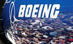 Люди отражаются в фюзеляже самолета Boeing 787 Dreamliner на заводе Boeing в Эверетте, США  8 июля 2007 года. Спрос на пассажирские самолёты растет, сказал глава Boeing Co Деннис Мюленберг в интервью французской газете Le Figaro. REUTERS/Robert Sorbo/File photo