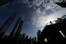 Un hombre camina en un puente en el distrito financiero de Pudong, en Shanghái, China. 22 de junio de 2016. Los incumplimientos de pagos de la deuda de China no representarán un riesgo sistémico siempre que el crecimiento económico siga dentro de un rango razonable, dijo el martes un funcionario de planificación estatal. REUTERS/Aly Song