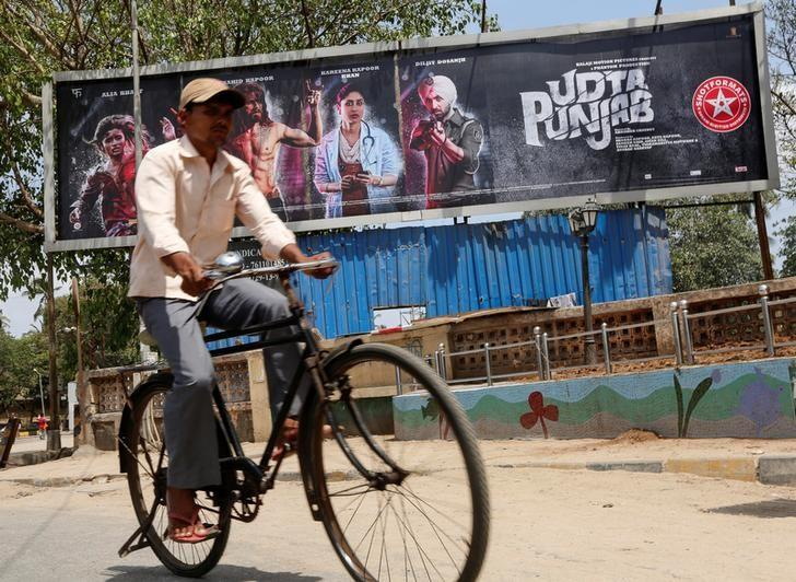 A man rides his bicycle past a poster of the movie ''Udta Punjab'' in Mumbai, India, June 13, 2016. REUTERS/Shailesh Andrade