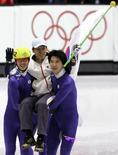 Seo Ho-Jin (242) and Oh Se-Jong (R) of South Korea carry their coach Song Jae-Kenn after the men's 5000 metres short track speed skating relay final at the Torino 2006 Winter Olympic Games in Turin, Italy, February 25, 2006.