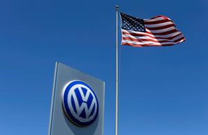 A U.S. flag flutters in the wind above a Volkswagen dealership in Carlsbad,...