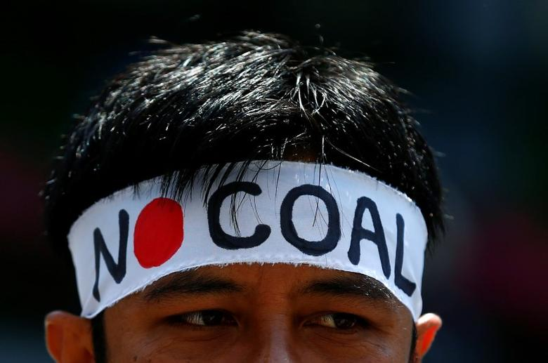 A demonstrator wears a headband during a protest in front of the finance ministry in Tokyo ahead of the upcoming Ise-Shima G7 summit, calling on Japan to stop investing in fossil fuels, Japan, May 19, 2016. REUTERS/Thomas Peter
