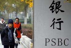 People walk past a sign outside a branch of Postal Savings Bank of China (PSBC) in downtown Beijing, China, November 12, 2015.   REUTERS/Kim Kyung-Hoon/File Photo