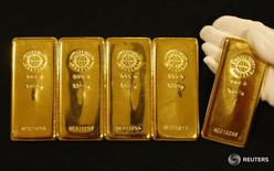 Слитки золота в магазине Ginza Tanaka в Токио 7 сентября 2009 года. Стоимость золота снизилась в четверг, поскольку более широкие рынки продемонстрировали признаки стабилизации, однако она все еще может показать максимальный месячный рост с февраля из-за решения Великобритании выйти из Европейского союза на прошлой неделе. REUTERS/Yuriko Nakao