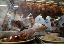 Hawker Derrick Lee, 30, sells chicken rice in his stall at a hawker centre in Singapore June 30, 2016. REUTERS/Edgar Su