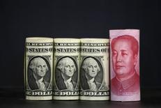 U.S. one dollar banknotes and a Chinese 100-yuan banknote are seen in a picture illustration, in Beijing, China, January 21, 2016. REUTERS/Jason Lee