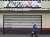 Cuatro empresas españolas informaron el miércoles que solicitaron ante el Banco Mundial un arbitraje para que le sea pagada una indemnización por la expropiación de sus inversiones en Venezuela, nacionalizadas en el 2010 por orden del fallecido presidente Hugo Chávez. En la imagen de aarchivo, un hombre camina junto a una tienda cerrada de la empresa Agroisleña en Caracas. REUTERS/Carlos Garcia Rawlins