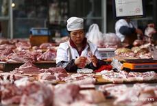 Женщина продает мясо на рынке в Куньмине, КНР 14 октября 2015 года. Мировые цены на продовольствие росли рекордными за четыре года темпами в июне из-за подъема цен на сахар и большинство других продуктов, сообщила Продовольственная и сельскохозяйственная организация ООН (ФАО) в четверг. REUTERS/Wong Campion