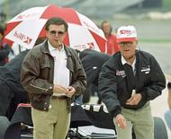 Carl Haas (L) watches the delivery of partner Paul Newman May 24, 1996 as they pitch quarters while waiting out a light rain in the pits of Michigan International Speedway during preparations for the May 26 inaugural U.S. 500.  Reuters/John C. Hillery