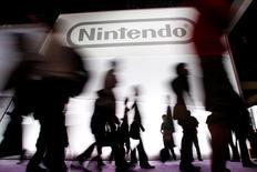 Las acciones de la compañía japonesa Nintendo se dispararon el viernes más de un 10 por ciento, impulsadas por las expectativas generadas por el juego para dispositivos móviles Pokemon Go, recientemente lanzado. En la imagen, varias personas caminan junto a un cartel con el logo de Nintendo en una exposición en Los Ángeles, el 7 de junio de 2011. REUTERS/Danny Moloshok/File Photo