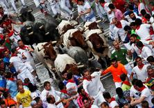 Runners lead Jose Escolar bulls and steers during the third running of the bulls at the San Fermin festival in Pamplona, northern Spain, July 9, 2016. REUTERS/Susana Vera