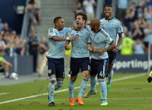 Jul 18, 2015; Kansas City, KS, USA; File photo of Sporting KC midfielder Benny Feilhaber (10) being congratulated by defender Amadou Dia (13) and defender Kevin Ellis (4) after scoring a goal during the first half of the match against the Montreal Impact at Sporting Park. Mandatory Credit: Denny Medley-USA TODAY Sports