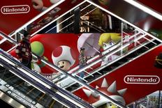Las acciones de la japonesa Nintendo Co Ltd se dispararon de nuevo el lunes, aumentando su capitalización bursátil en 7.500 millones de dólares en dos días, al celebrar los inversores el éxito de Pokemon GO - la primera de su muy esperada incursión en los juegos móviles. En la imagen de archivo, se ven personas en escaleras mecánicas pasando junto a un anuncio de la compañía japonesa en grupo de distribución de electrónica en Tokio, el 25 de abril de 2016. REUTERS/Thomas Peter