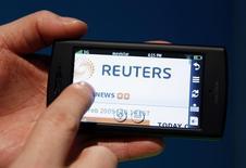 En la imagen de archivo, un hombre sujeta un teléfono donde mira la página web de noticias de Reuters News, en Barcelona, el 16 de febrero de 2009. Thomson Reuters Corp dijo el lunes que acordó vender su división de propiedad intelectual y ciencia a las firmas de capital privado Onex Corp y Baring Private Equity Asia por 3.550 millones de dólares en efectivo. REUTERS/Albert Gea