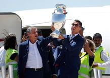 Portugal's head coach Fernando Santos and Cristiano Ronaldo step off their airplane holding the EURO 2016 cup as their arrive home in Lisbon, Portugal, July 11, 2016.     REUTERS/Rafael Marchante