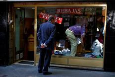 La Fundación de las Cajas de Ahorros (Funcas) anunció el martes que ha elevado su previsión de crecimiento sobre la economía española en 3 décimas hasta el 3 por ciento mientras que mantuvo la de 2017 en el 2,3 por ciento por los efectos negativos del brexit. En la imagen de archivo, un hombre mira el escaparate de una tienda en Madrid mientras un empleado cambia los precios de la ropa, el 31 de julio de 2013. REUTERS/Susana Vera