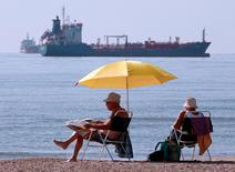 People sunbathe as oil and gas tankers are anchored off the Fos-Lavera oil hub near Marseille, southeastern France, October 7, 2010.   REUTERS/Jean-Paul Pelissier/File Photo
