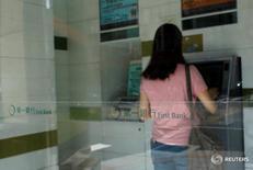Женщина снимает деньги в банкомате First Bank в Тайбэе 13 июля 2016 года. Тайваньские следователи подозревают двух хакеров из России во взломе банкоматов крупнейшего банка страны и краже более $2 миллионов из десятков аппаратов. REUTERS/Tyrone Siu