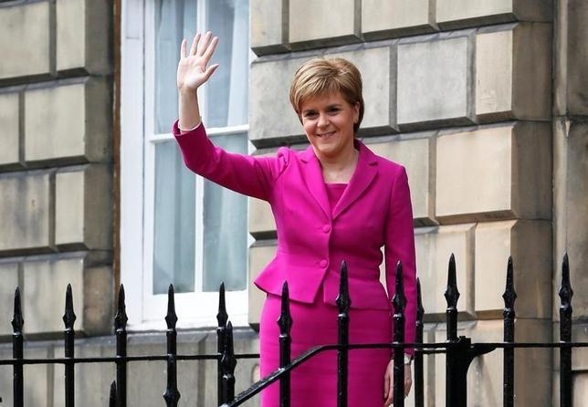Scotland's First Minister and SNP leader Nicola Sturgeon waves as she stands outside Buth House, her official residence in Edinburgh, Scotland, Britain May 6, 2016. To match Insight BRITAIN-EU/STURGEON    REUTERS/Russell Cheyne/File Photo