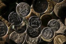 Рублевые монеты. Рубль снижается утром пятницы за счет реального спроса на сильно подешевевшую накануне валюту, а также на фоне текущей отрицательной динамики нефти, далее он будет зависеть, в том числе, от активности экспортеров, продающих валютную выручку под налоги и дивиденды, благодаря чему рубль достиг пиков текущего года. REUTERS/Maxim Zmeyev