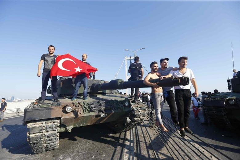 People pose near a tank after troops involved in the coup surrendered on the Bosphorus Bridge in Istanbul, Turkey July 16, 2016.  REUTERS/Murad Sezer