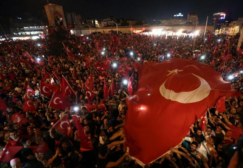 Supporters of Turkish President Tayyip Erdogan wave national flags as they gather at Taksim Square in central Istanbul, Turkey, July 16, 2016. REUTERS/Huseyin Aldemir