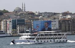 Пассажирский паром проходит в Босфорском проливе мимо предвыборного плаката Тайипа Эрдогана. Стамбул, 7 августа 2014 года. Неудавшаяся попытка государственного переворота турецкими военными, совершенная в ночь на субботу, временно заблокировала движение судов через Босфорский пролив, напомнив миру об усиливающейся роли Турции в качестве транзитного узла для транспортировки сырьевых товаров между Россией, Центральной Азией и Европой. REUTERS/Murad Sezer