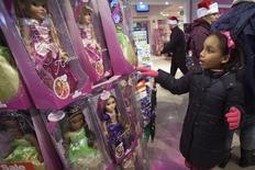 """Девочка у игрушек Disney Princess в магазине Toys R Us в Нью-Йорке. 27 ноября 2014 года. Производитель игрушек Hasbro Inc сообщил о превысившей ожидания квартальной прибыли и выручке благодаря уверенному спросу на куклы серий Disney Princess и Frozen, а также игрушки-трансформеры по мотивам """"Звёздных войн"""". REUTERS/Carlo Allegri"""