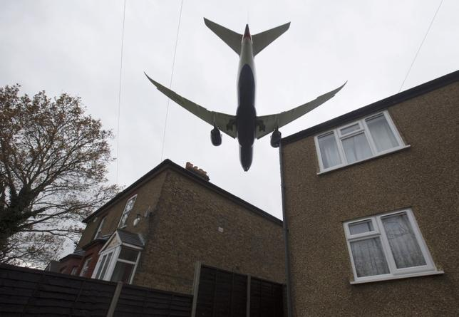An aircraft  passes over houses as it lands at Heathrow Airport near London, Britain, December 11, 2015.  REUTERS/Neil Hall