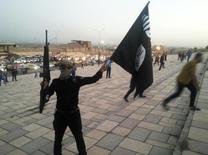 Militante segurando arma e bandeira do Estado Islâmico em Mosul.    23/06/2014        REUTERS/Stringer