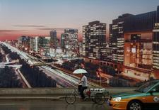 Un hombre en un triciclo pasa junto a una publicidad que muestra una vista de Pekín al anochecer, en Pekín, China. 19 de julio de 2016. La economía de China está creciendo, pero apenas a la mitad del ritmo estimado oficialmente, mostró el martes un sondeo privado entre gerentes de ventas. REUTERS/Thomas Peter