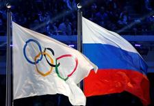 The Russian national flag (R) and the Olympic flag are seen during the closing ceremony for the 2014 Sochi Winter Olympics, Russia, February 23, 2014.  REUTERS/Jim Young/File Photo