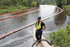 A cleanup worker watches the absorbent booms collecting oil from the Kalamazoo river after an oil  pipeline, owned by Enbridge Energy Partners, leaked an estimated 820,000 gallons of oil into the Kalamazoo river in Western Michigan, near Marshall July 31, 2010.   REUTERS/Rebecca Cook/File Photo