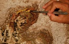 "A worker cleans a mosaic mural depicting Apollo and the Muses found in an archaeological site under the ""Terme di Traiano"" in downtown Rome July 29, 2011. Picture taken July 29, 2011. REUTERS/Tony Gentile/File"