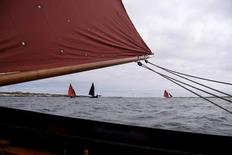 Galway Hooker are seen near MacDara's Island off the coast of Galway, Ireland, July 16, 2016. Seafarers and other members of the Carna community make an annual pilgrimage to MacDara's Island, home to a 6th Century oratory, to attend a mass for St. MacDara, the patron saint of fishermen. The pilgrimage is believed to keep seafarers safe throughout the year. REUTERS/Clodagh Kilcoyne